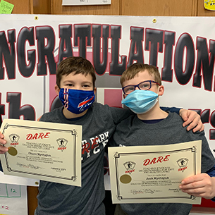 Brothers from Ellicott Elementary proudly display their D.A.R.E. graduation certificates.