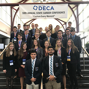 Thirty DECA students at State Career Conference stand on the stairs.