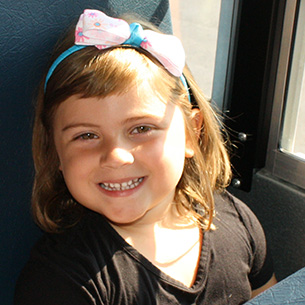 Female student pictured smiling on the bus.