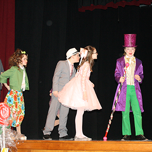willy wonka and 3 other characters on stage