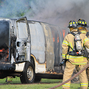 a burning van with two firefighters standing nearby