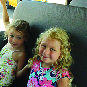 two girls smiling on a bus