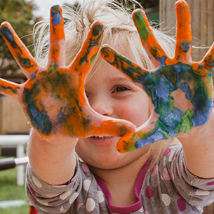 Little girl holding up her hands with paint all over them